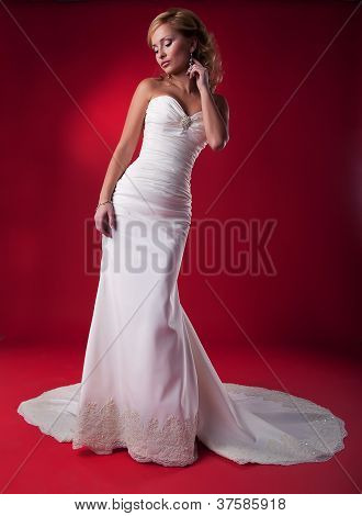 Pretty Bride In White Wedding Long Dress On Red Background