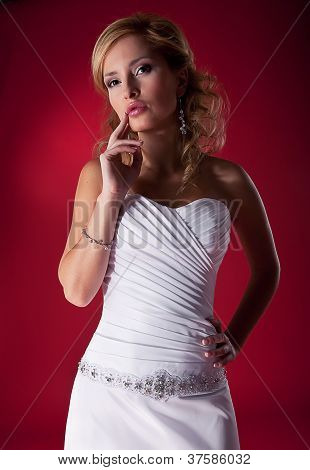 Fasion Model Blonde In Wedding Dress Posing Over Red Background