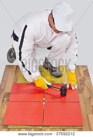 Worker Applies Ceramic Tiles On Wooden Floor With Rubber Hammer