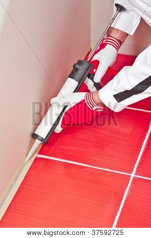 Worker Applies Silicone Sealant On Corner Wall Tiles