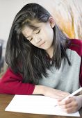 image of ten years old  - Ten year old biracial girl writing or drawing on paper - JPG