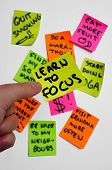 stock photo of soulmate  - A hand holding a post it note with the words: LEARN TO FOCUS over a bunch of post it notes with written goals or tasks that have to be accomplished.