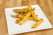 stock photo of rutabaga  - White plate of rutabaga fries on wood - JPG