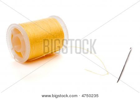 A Yellow Spool Of Thread And A Needle