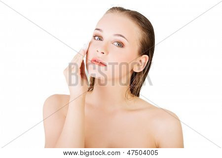 Portrait of happy young woman cleaning skin by cotton pad, over white background