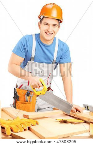 Manual worker with helmet cutting wooden batten with a saw isolated on white background