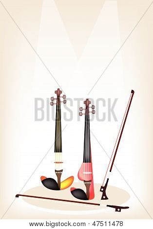 Two Beautiful Modern Violins On Brown Stage Background