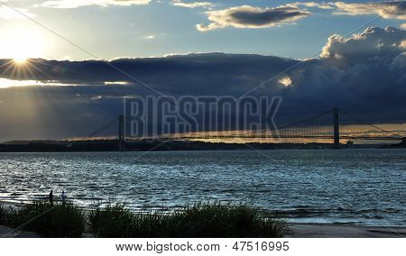 Sunbeams coming through the clouds at sunset time on Hudson river