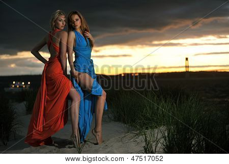 Two fashion model posing in red and blue dresses on sunset time