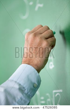 Closeup of male teacher's hand writing on greenboard in classroom