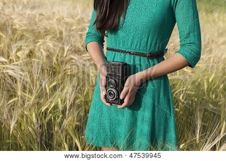 Brunette Girl With Retro Camera In Meadow