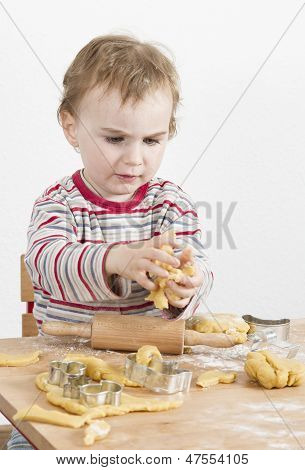 Young Child With Dough In Grey Background