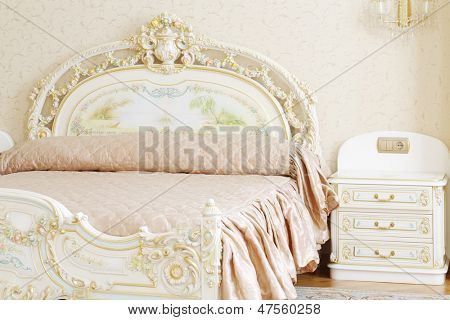 Luxurious bedroom with white double bed and bed-side table in classic style.