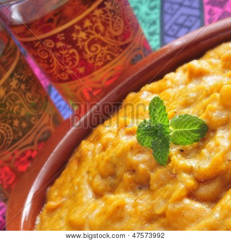 closeup of a earthenware bowl with korma curry and some ornamented glasses with tea