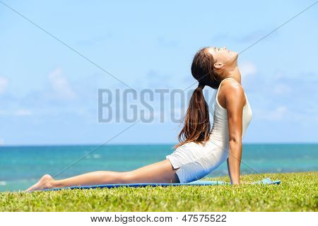 Fitness yoga woman stretching abdominal stomach muscles in cobra posture, bhujangasana. Fit fitness girl stretching out after exercising outside on beach in summer. Beautiful multiracial female model.