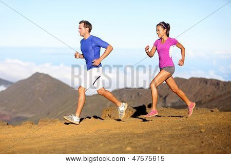 Running sport - Runners couple in trail run outside in amazing nature. Fit young sports multiracial fitness couple training cross country running together. Asian woman, Caucasian man in full body.