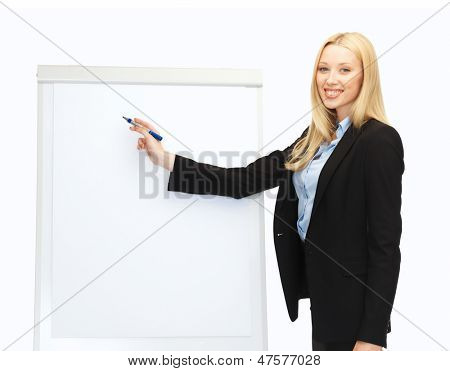 bussiness and education - businesswoman writing on flipchart in office