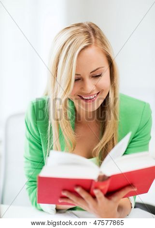 picture of smiling young woman reading book at school