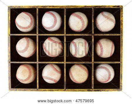 A dozen scuffed baseballs in a divided wooden box. Horizontal format over white.