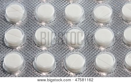 Glossy Packaging Of Several Rows Of White Tablets