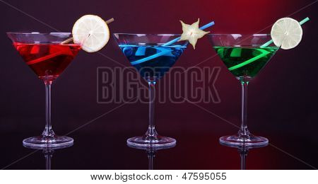 Alcoholic cocktails in martini glasses on dark red background