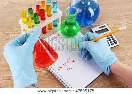 Hand scientist writing formulas
