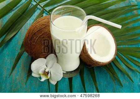 Cocos con vaso de leche, en el fondo azul de madera