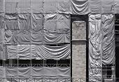 Building Covered With Wrinkled Tarpaulin Canvas