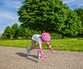 Preschool girl with inline roller skates on, falling down