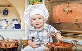 Постер, плакат: маленький мальчик сидит на кухонный стол и играет повар