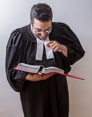 picture of toga  - Man in canadian lawyer toga holding a book of law laughing at it - JPG
