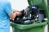 stock photo of garbage bin  - Man discarding old electronics int the plastic bin - JPG