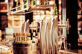 stock photo of over counter  - Glass of beer on pub over blurred background - JPG