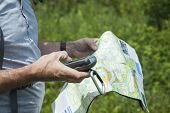 stock photo of gps  - Man with gps in hand and map in other hand during a hike - JPG