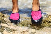 Water shoes in Pink neoprene on rocks in water on beach. Closeup detail of the feet of a woman weari