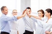 stock photo of office party  - picture of happy business team celebrating victory in office - JPG