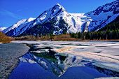 stock photo of snow forest  - Partially Frozen Lake with Mountain Range Reflected in the Great Alaskan Wilderness - JPG