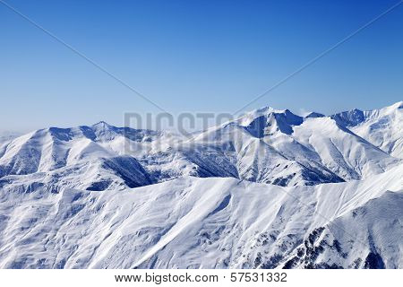 Snowy Winter Mountains And Blue Sky, View From Ski Slope
