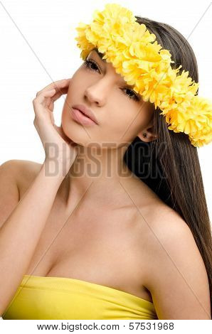 Portrait of a sexy woman with wreath of yellow flowers on the head.