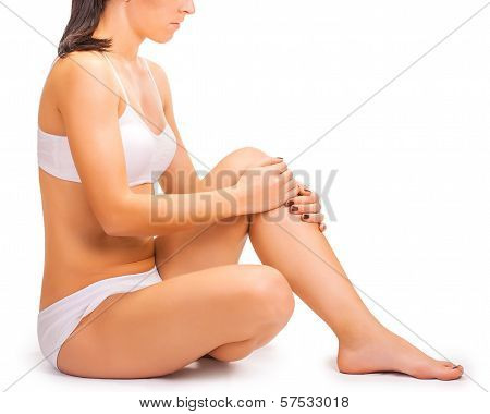 pain. girl holds knee in his hands. isolated