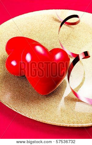 Two Red Hearts On Golden Plate On Red Festive Napkin With Red Ribbon Close Up. Valentines Day Backgr