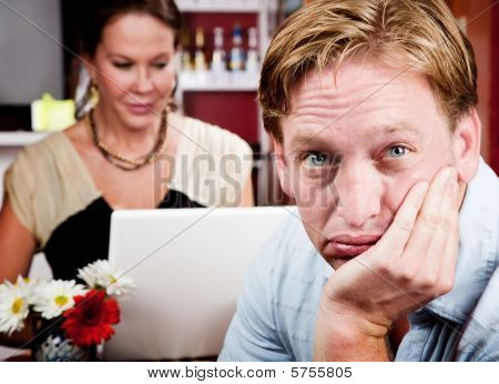 Bored Man With Woman On Laptop Computer