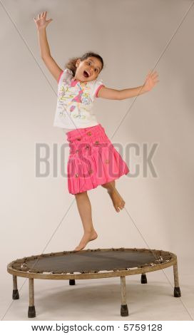 a young pretty girl enjoying herself jumping on the tampourine