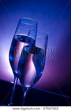 Champagne Flutes On Bar Table On Dark Blue And Violet Light Background