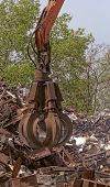 image of scrap-iron  - inustrial machine with scrap metal grapple in front of scrap iron