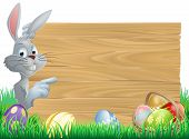 foto of ester  - White Easter rabbit bunny peeking round a sign and pointing chocolate Easter eggs and basket in front - JPG