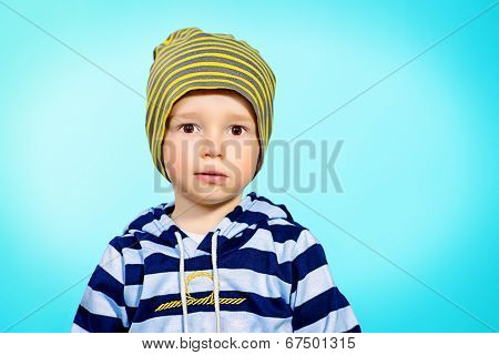 Portrait of a cute 2 years old boy over blue background. Childhood.