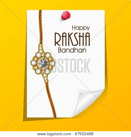 Rakhi with a paper note on bright yellow background on the occasion of Happy Raksha Bandhan.