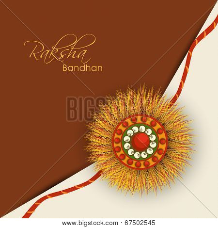 Beautiful rakhi design on brown and beige background on the occasion of Happy Raksha Bandhan.