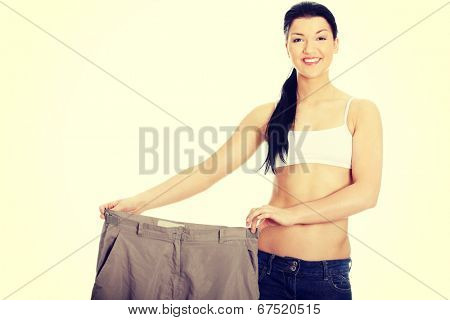 Young happy woman showing how much weight she lost.